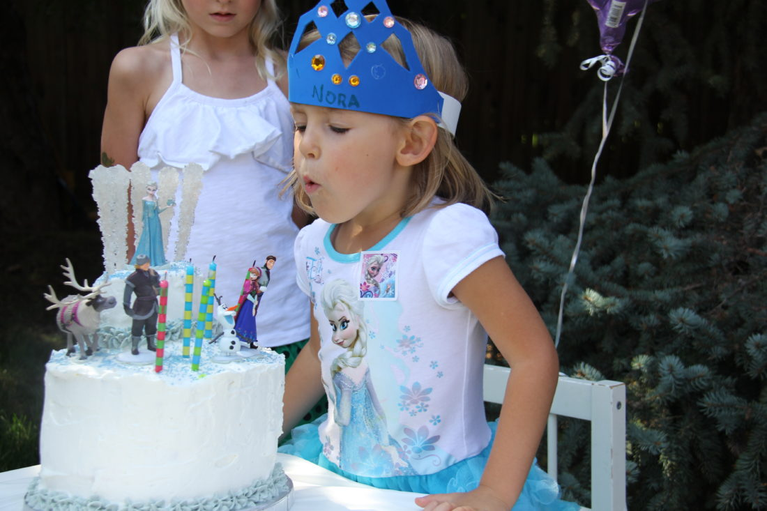 Nora blowing out candles on her Frozen cake