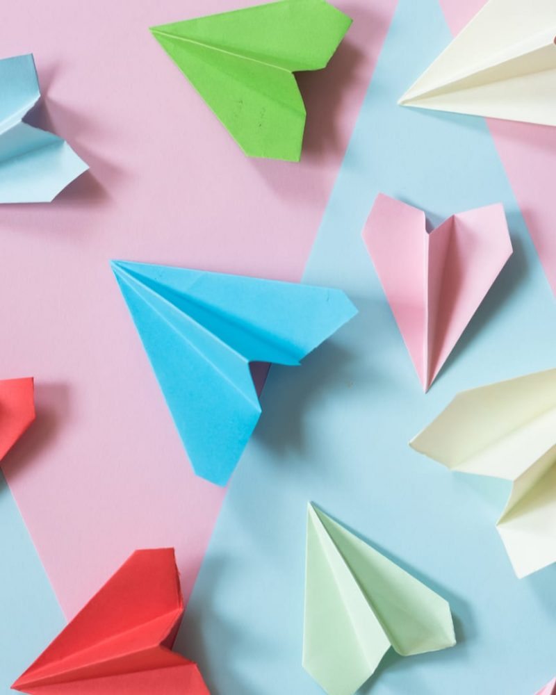 multicolored paper airplane layed out on pink and blue paper